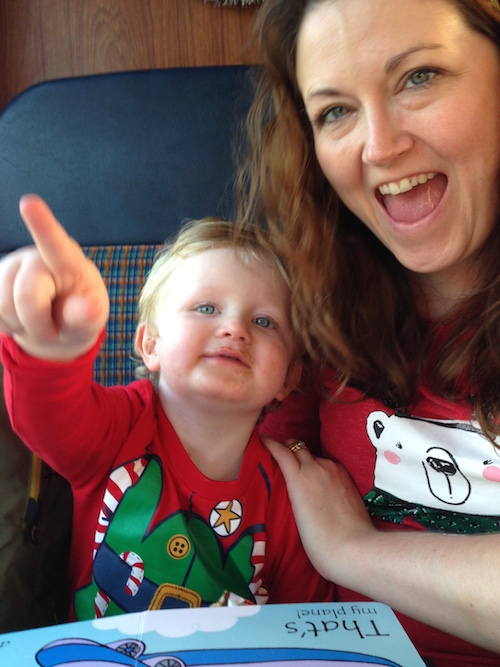 Mattie on the Santa train, eating chocolate with Mummy. Both have just spotted Santa walking down the train.