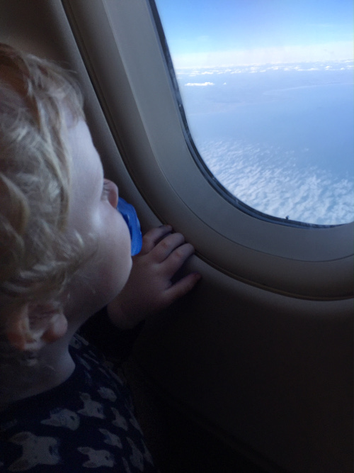 Mattie looking out of the Plane Window, doddie in mouth